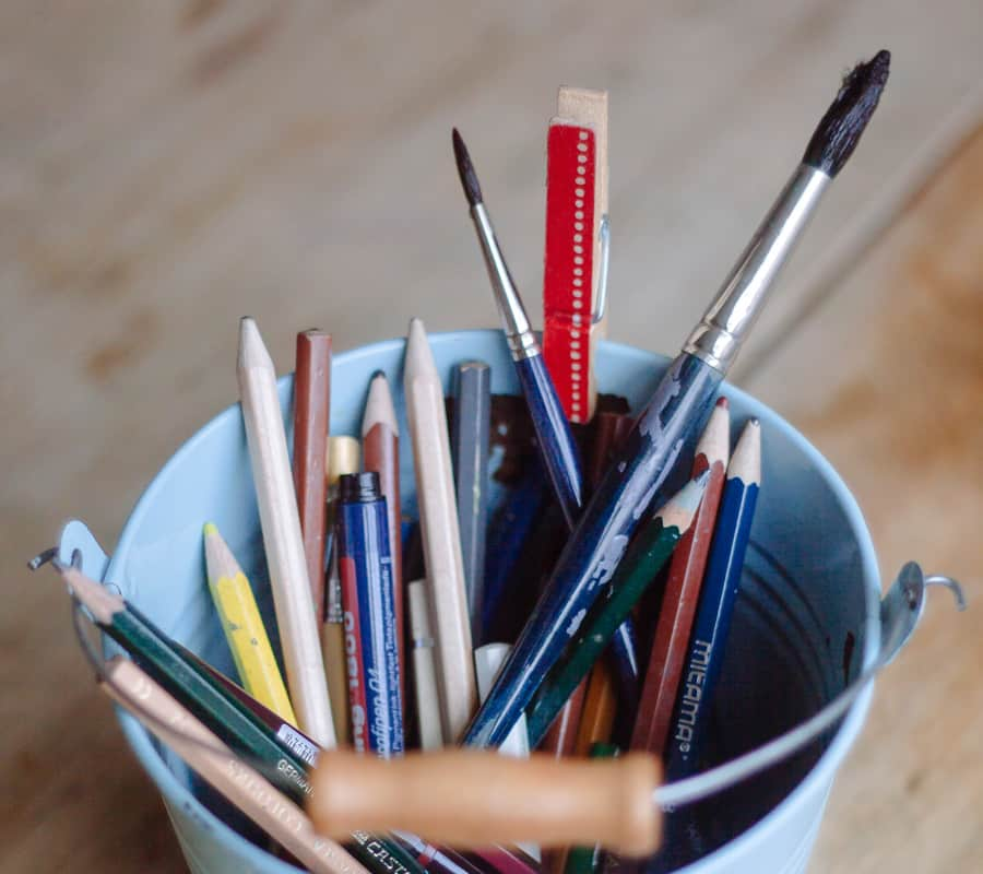 paint pail with artist pencils and paintbrushes