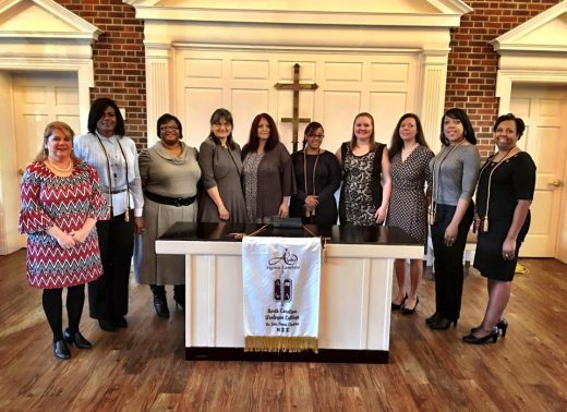 10 female adult students smiling for picture in the chapel