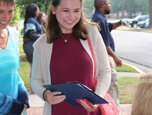 Smiling student with parent receiving a check-in packet and talking with a representative