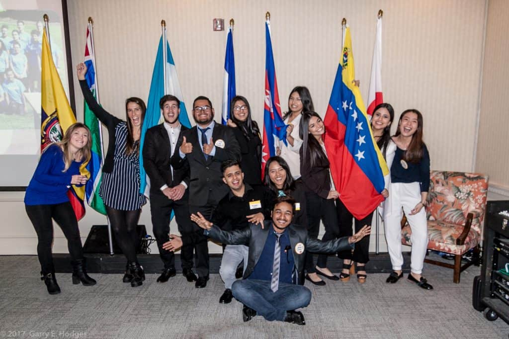 12 joyous international students posing with native country flags