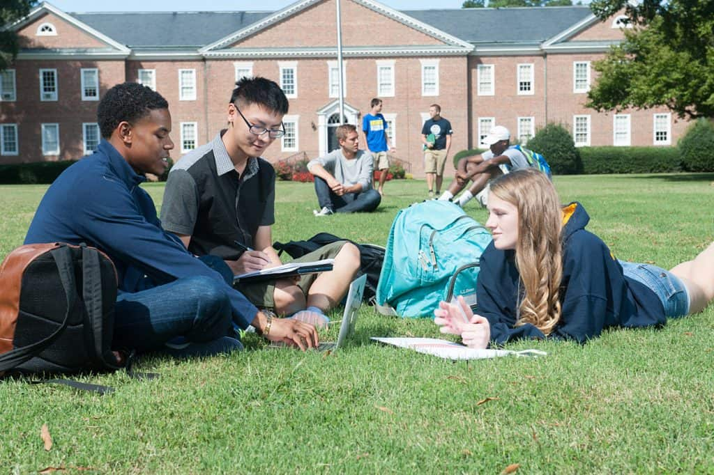 3 students studying together on one of the many green grass fields on campus in front of the flag pole