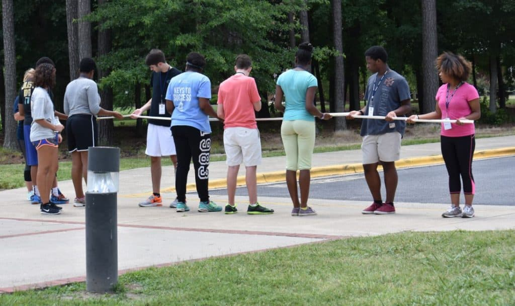10 youth standing together and participating in a group team building challenge