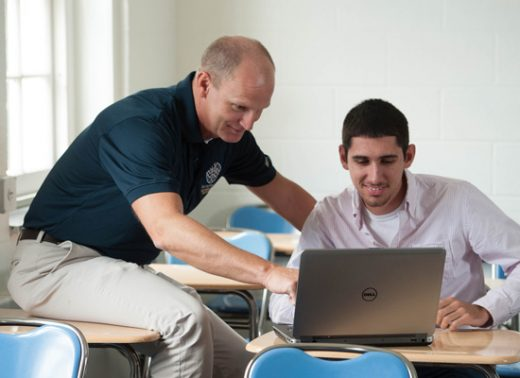 friendly teacher helping student on a laptop in a classroom