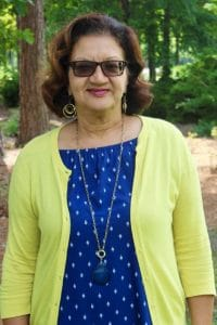 Woman wearing glasses, a blue dress, and a yellow jacket.