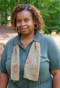 African-American woman with wavy brown hair in grey shirt and a scarf.