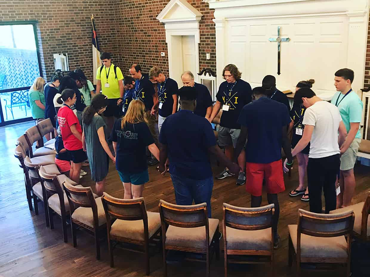 YTI Students and staff holding hands while praying in the chapel
