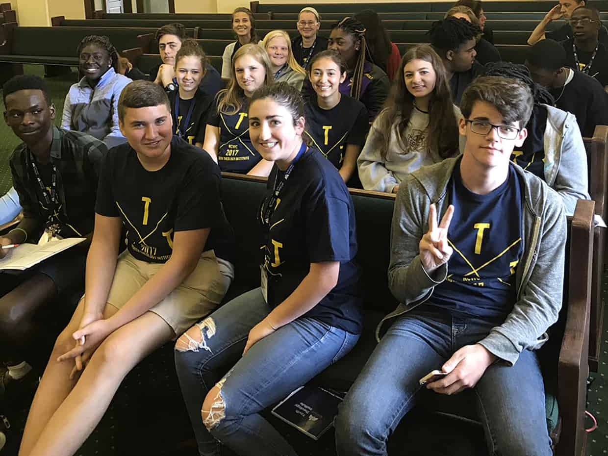 students and staff smile at the camera as they wait in church pews