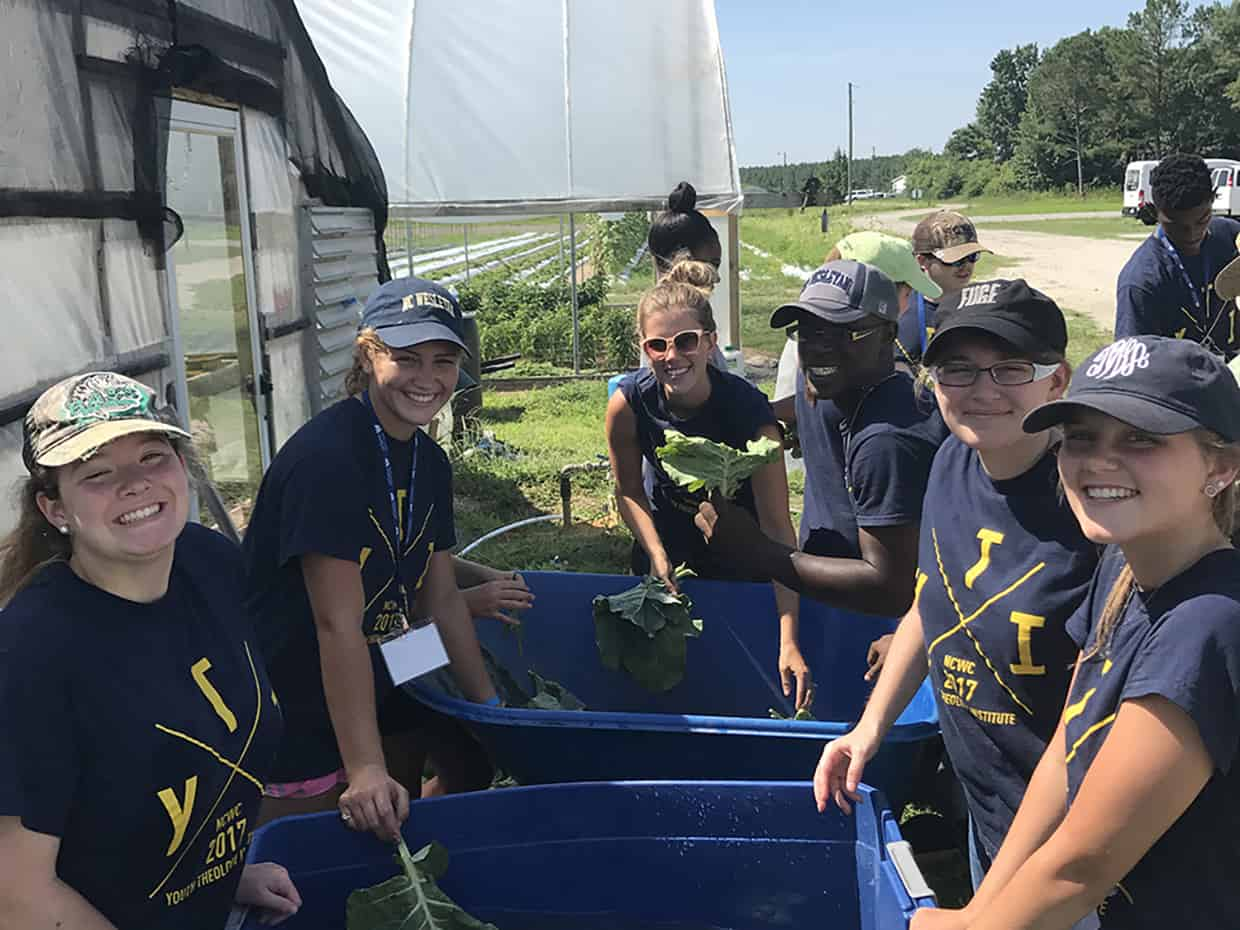 9 students and counselors working at a garden