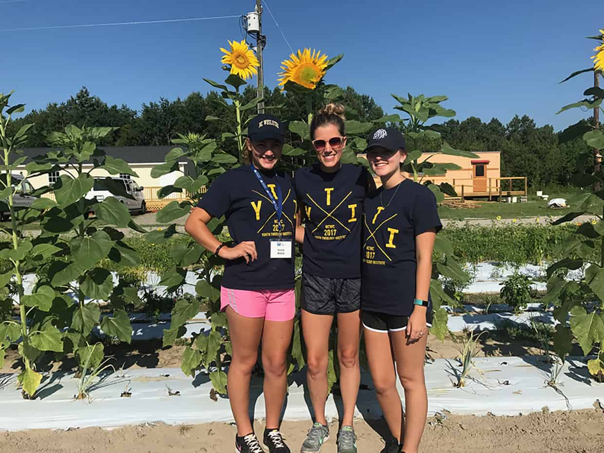 3 YTI students posing in front of giant sunflowers at a service project