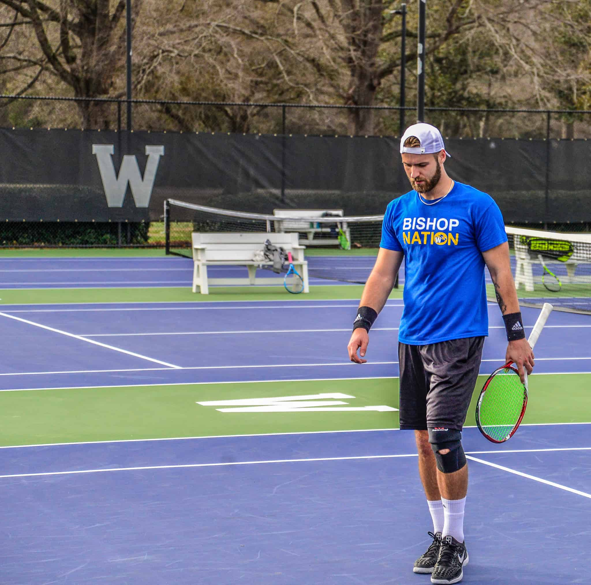 Male tennis player in blue Bishop Nation shirt holding a racket
