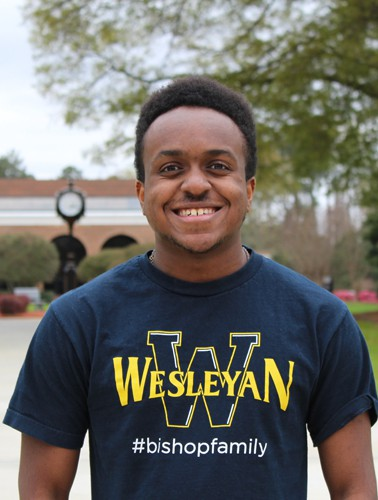 Smiling African American male wearing a Navy Wesleyan shirt