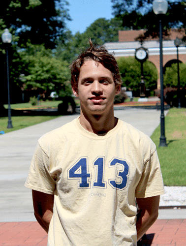 Male student with brown hair wearing a 413 class Wesleyan shirt