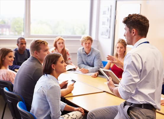 Young male teacher engaging with students around a table during class