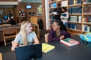 Two female students in library working together