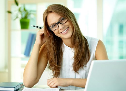 A young woman with brown hair and glasses smiling while working at a desk.