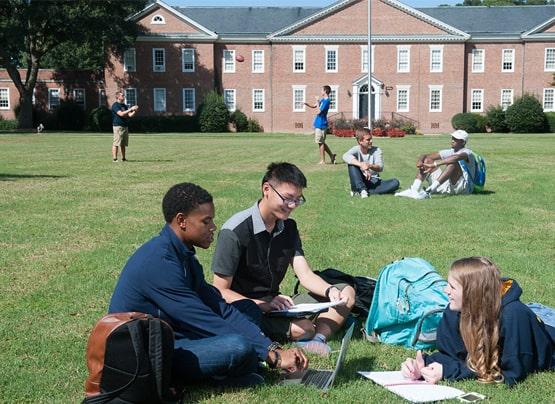 Students joyfully work together on the front lawn in front of Braswell Admin Building