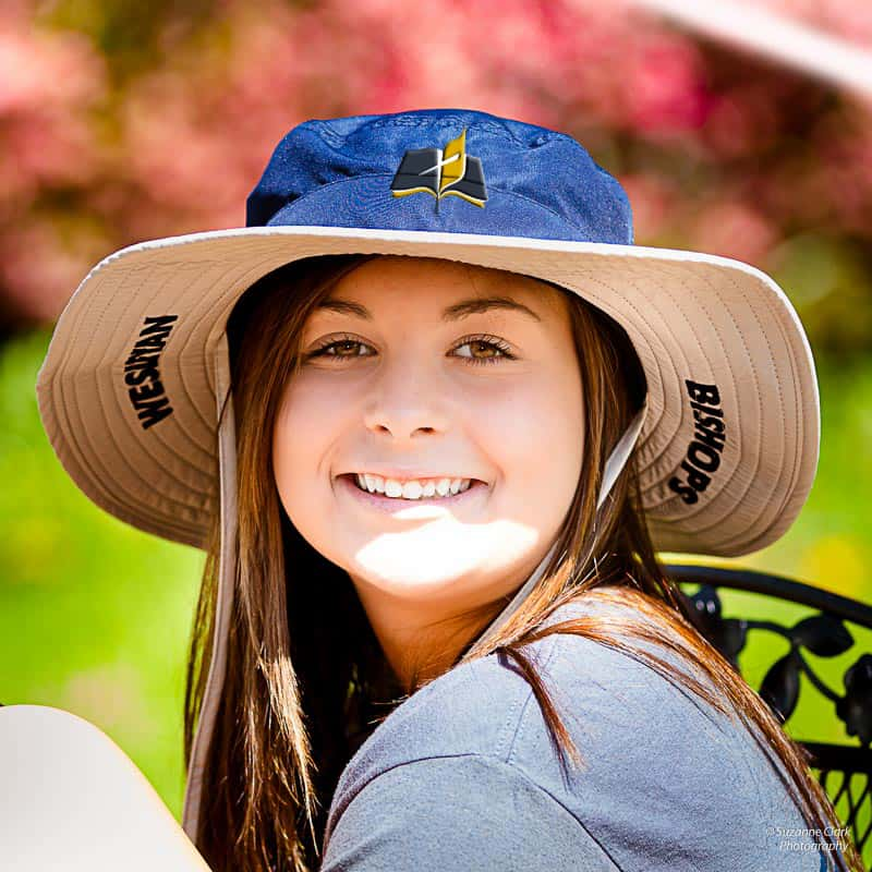 Smiling female student with long brown hair wearing a Wesleyan Bishops rimmed hat