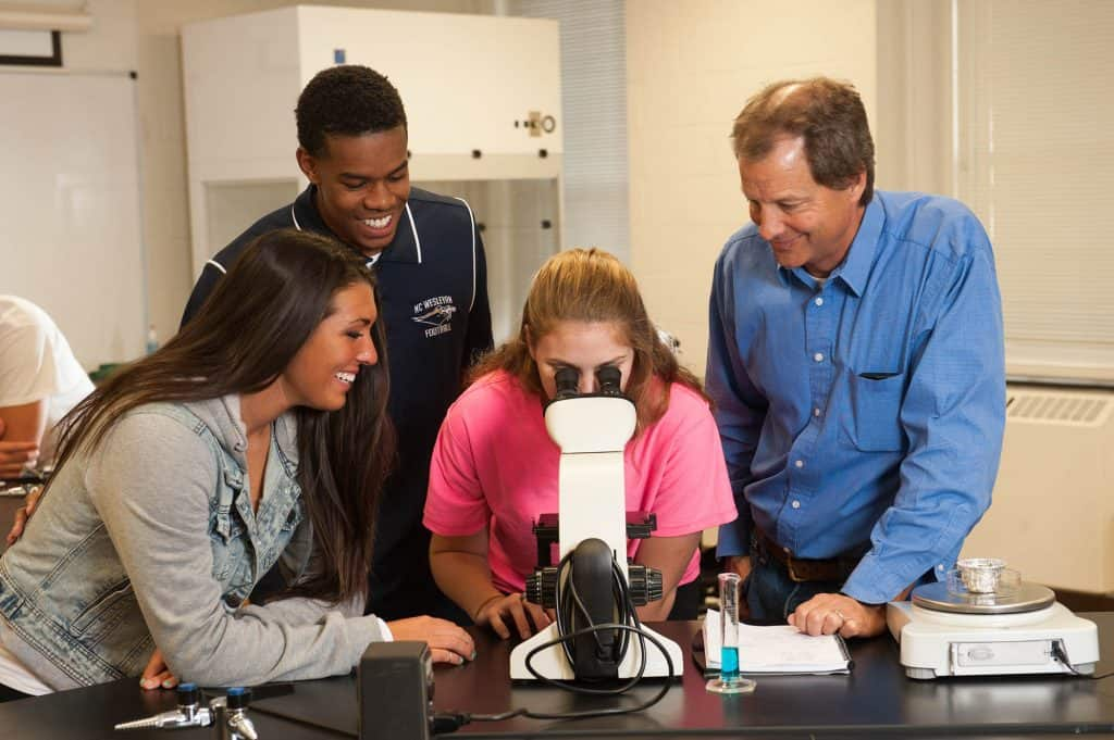 Students and teacher gathered around a microscope