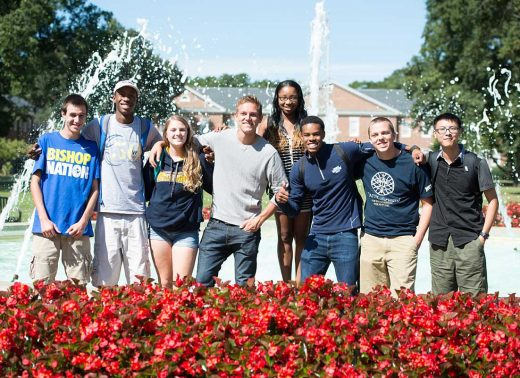 8 Students with arms around each others posing for picture in front of fountain