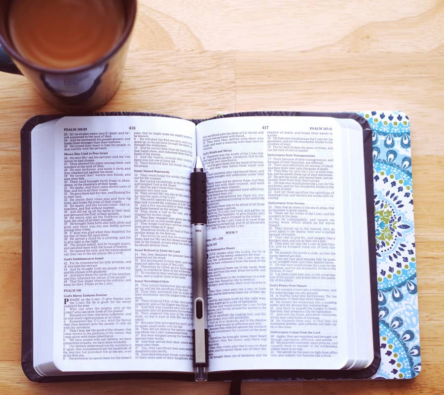 bible on table with writing pen in the middle