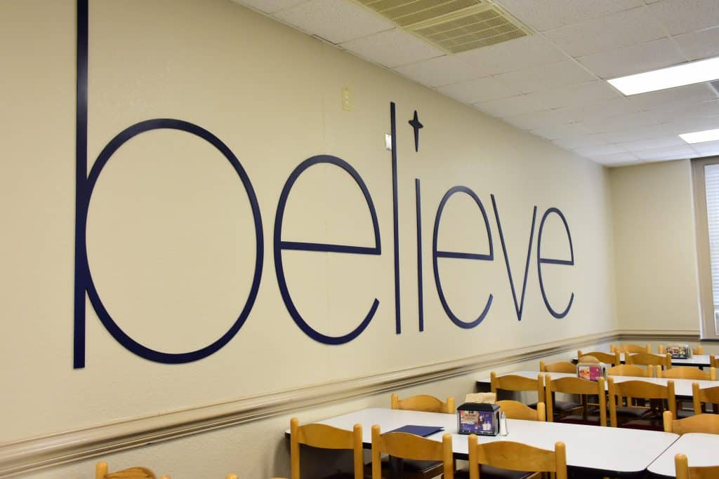 "White wall in the cafe with navy-blue ""Believe"" text decorations"