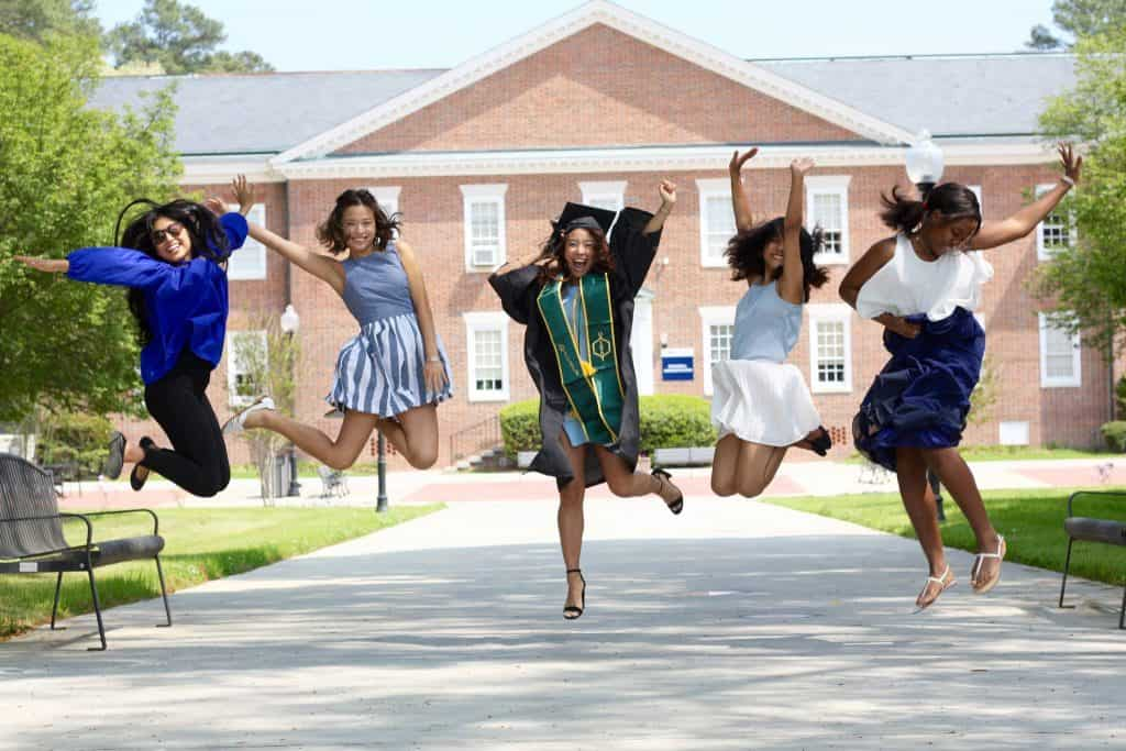 5 women in midair jumping with cap and gown woman in the middle