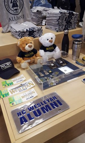 Merchandise table with teddy bears, shirts, and various other Wesleyan products