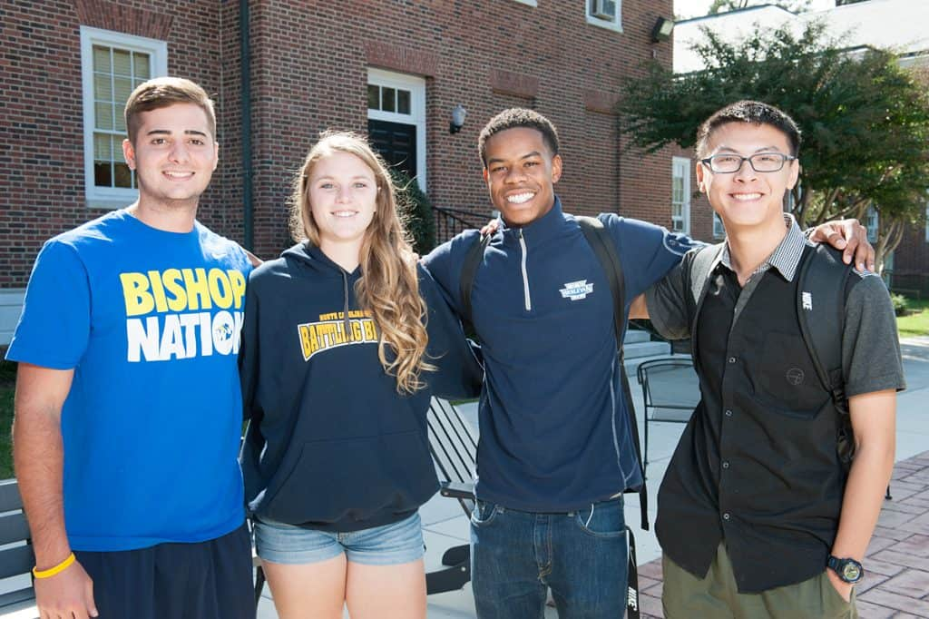 4 smiling students posing together on the patio on campus
