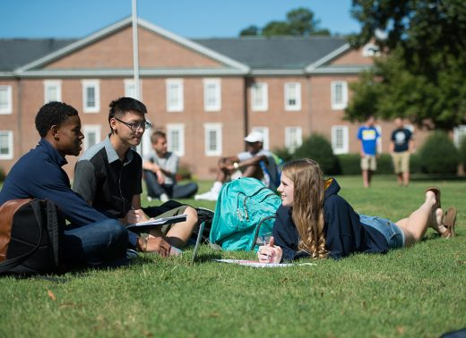 3 students studying together on one of the many green grass fields on campus