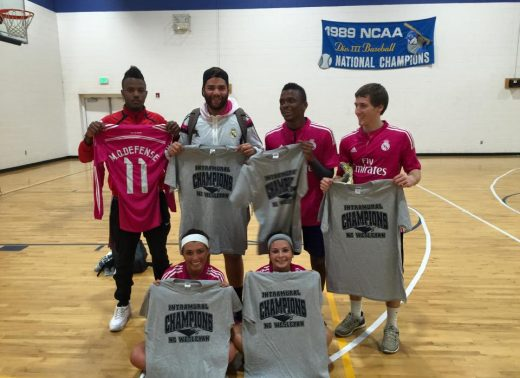 "4 male and 2 female students wearing matching pink shirts holding grey ""Intramural Champions"" shirts"