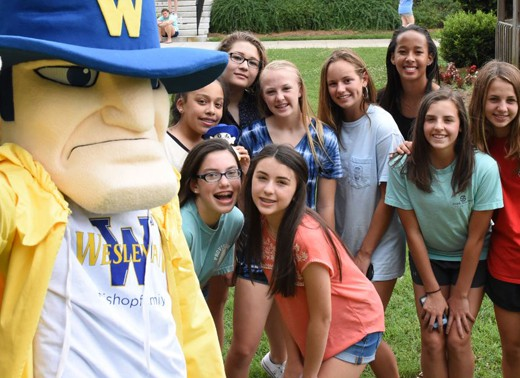 9 teen girls posing with Wes the mascot