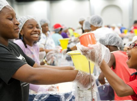 Joyful young individuals putting together meals for those who are in need