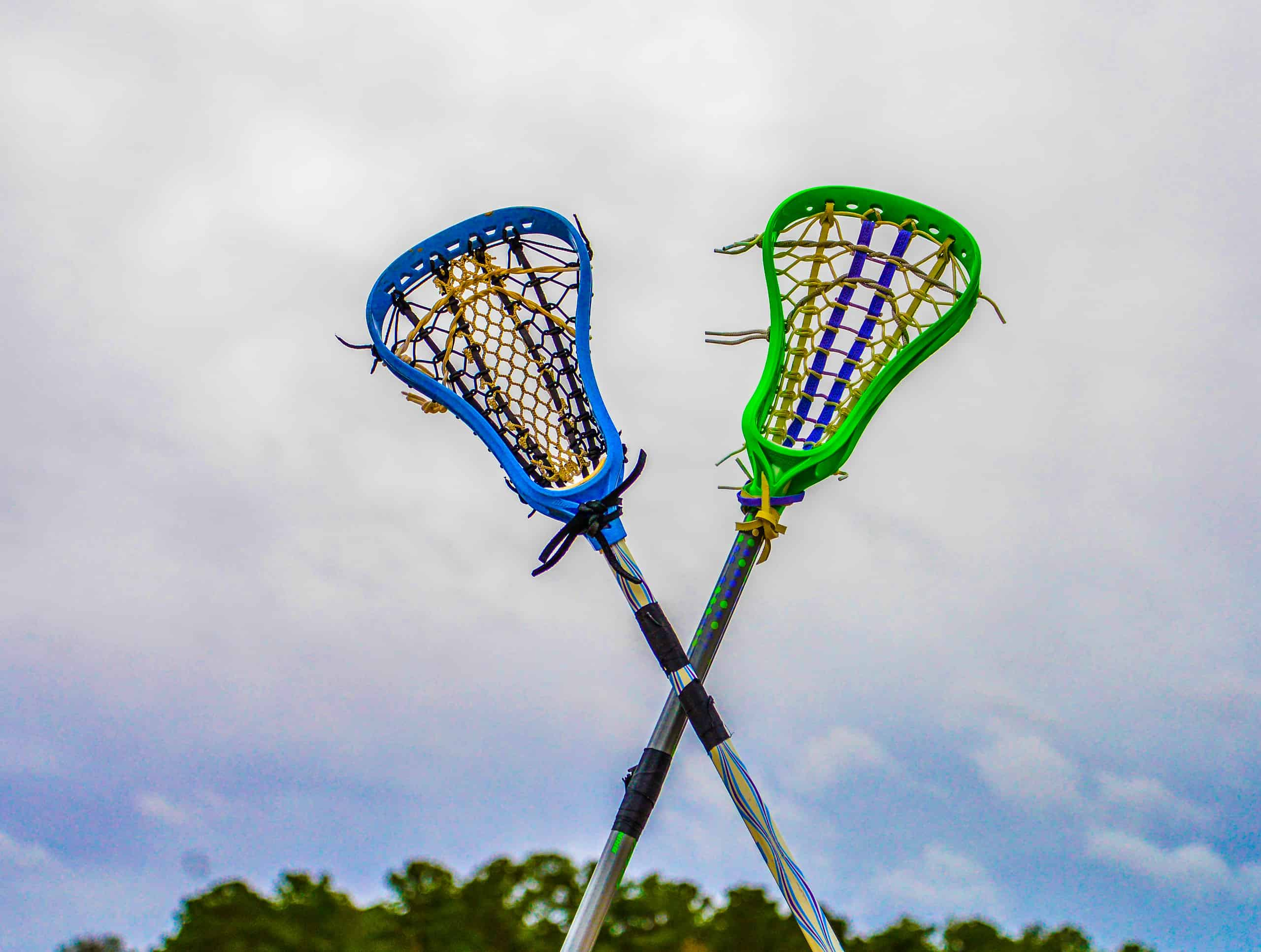 "Two lacrosse sticks crossed in the air in an ""X"" shape with trees and sky in the background."