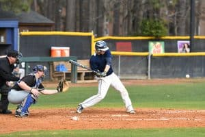 Bishop baseball player in blue and gold uniform swinging at an approaching baseball.