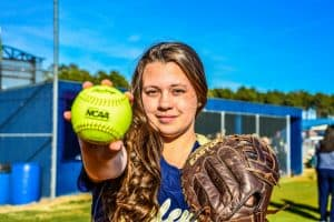A bishop softball player in blue and gold jersey holding a softball and wearing a softball glove.