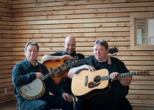 Three middle-aged men sitting down holding their instruments.
