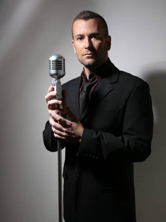 Young man, Terry Barber, posing with singing mike and wearing a black suit.