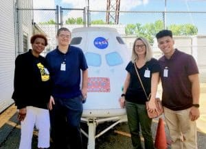 Dr. Brewer and students standing in front of NASA return capsule