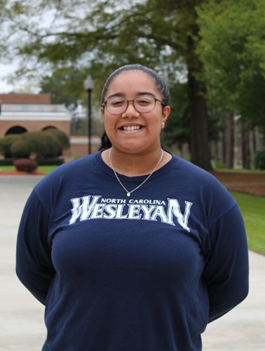 Puerto Rican Female smiling with navy Wesleyan shirt
