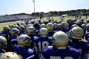 Overhead shot of football team in gold helmets and navy jerseys huddled before the game