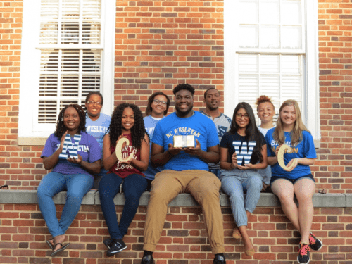 Students sitting on a brick wall hold NCWC letters
