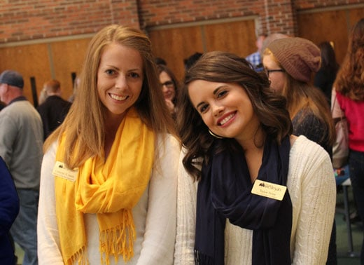 a blonde woman wearing a yellow scarf standing next to a brunette wearing a navy blue scarf