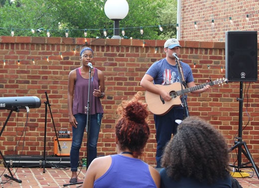 Female singer and male guitarist performing on a brick patio