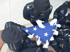 NCWC ROTC Students folding American flag during ceremony