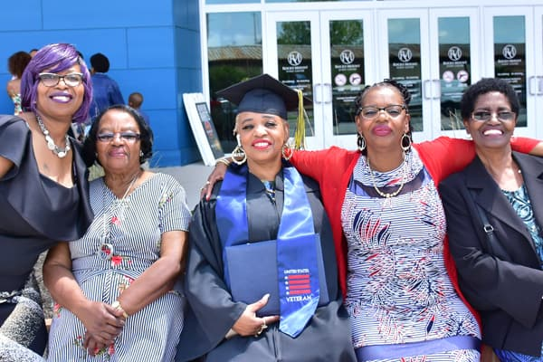 adult graduating college with family